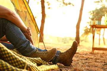 Young man sitting in camping tent in forest Fotomurales