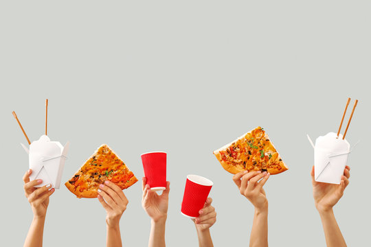 Many hands with delivery food on grey background