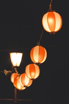 Orange paper lanterns hanging from a wire spreading light during nighttime