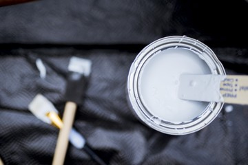 Overhead shot of a wooden pain mixer in the paint can with a blurred background