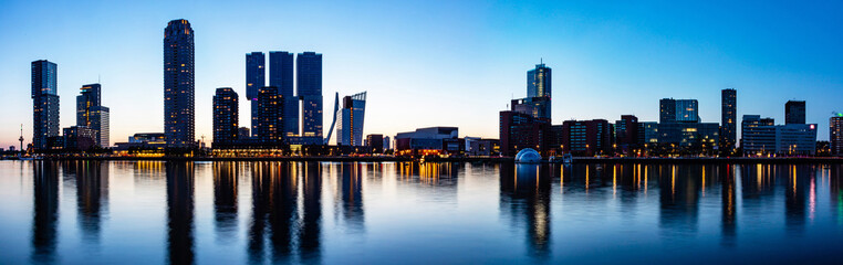 Rotterdam Netherlands skyline night panorama. City towers illuminated, reflections on the water, sunset time
