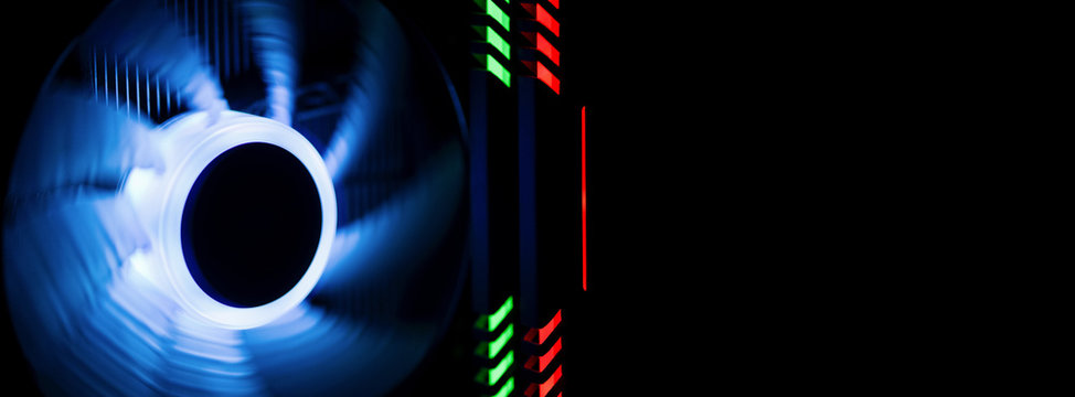 Banner. Fragment of the computer case. Powerful computer cooler in motion with blue backlight, next to the highlighted RAM green and red