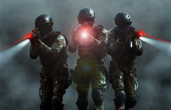 Special force assult team at night with laser sights and smoke screen background