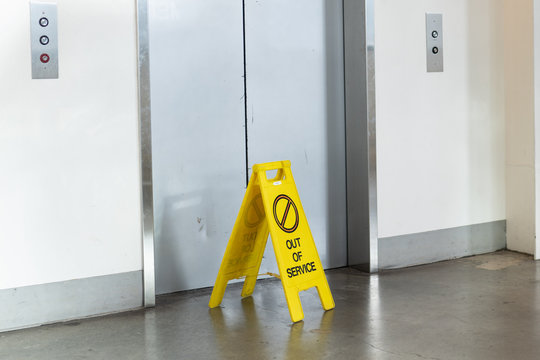 """Elevator with an """"Out of service"""" yellow sign in front of it."""