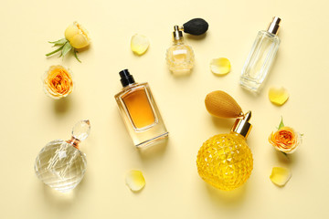 Flat lay composition with different perfume bottles on light yellow background