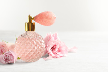 Vintage bottle of perfume and flowers on light background, space for text