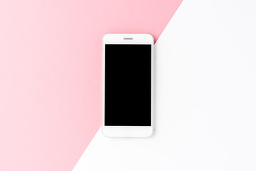 Smart phone with empty screen on abstract pink and white background. Top view