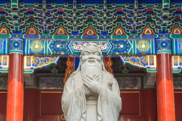Confucius statue in front of colorful ancient temple with beautiful ornaments