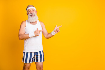Photo of aged model white hair guy directing fingers empty space advising choose healthy sports supplements wear tank-top shorts sweatband isolated yellow color background