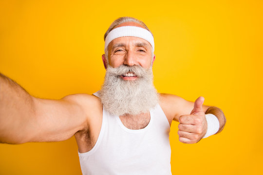 Photo of aged model white hair guy making blog selfies videos while practicing raising thumb up wear tank-top hair hands sweatband isolated yellow color background