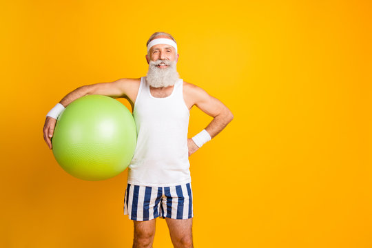 Photo of positive cheerful handsome old man holding fit ball smiling toothily with hand on waist standing confidently near empty space isolated vivid yellow color background