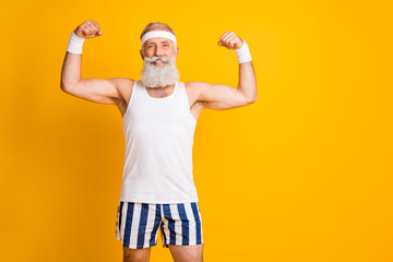 Photo of handsome cheerful positive man old smiling toothily demonstrating biceps near empty space isolated vivid yellow color background