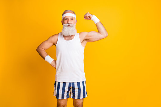 Photo of cheerful positive attractive handsome old man demonstrating his muscles looking intently at you holding hand on waist isolated vivid color yellow background