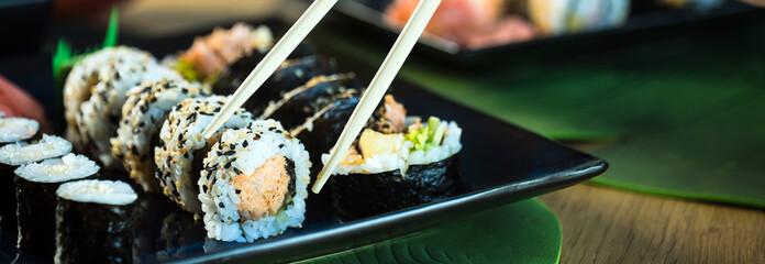 Foto op Plexiglas Sushi bar Sushi Set. Various rolls on a wooden plate. On dark rustic background