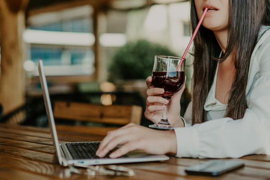 Woman sitting in coffee shop drink juice and using phone