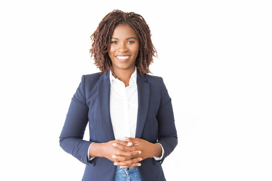 Happy cheerful female consultant looking at camera. Young African American business woman with clasped hands standing isolated over white background, smiling. Happy entrepreneur concept