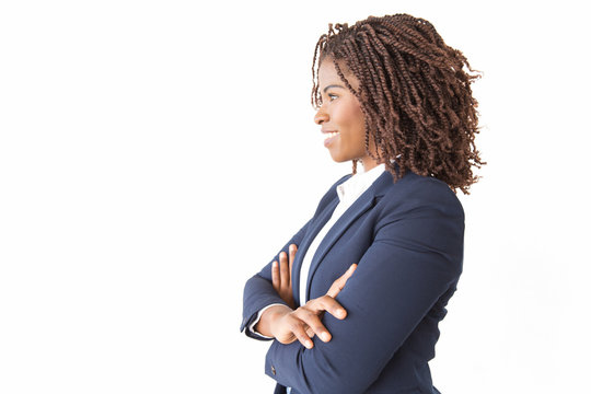 Happy successful female professional looking at copy space away. Young African American business woman with arms crossed standing isolated over white background. Advertising concept