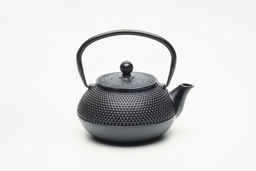 Black cast iron teapot on a white background.