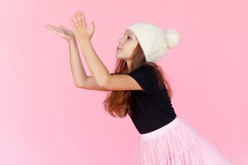 Profile portrait of a cute little girl in white wool hat on pink background, blowing a side part. Space for text.