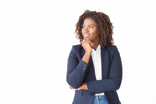 Happy pensive female agent looking at copy space away. Young African American business woman standing isolated over white background, leaning chin on hand, smiling. Advertising concept