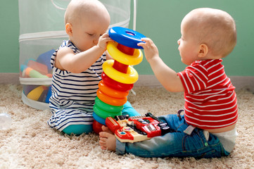 Educational logic toys for children. Twins collect a colored pyramid. Montessori games for the development of the child. Early development
