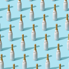 Trendy Christmas pattern made with white champagne bottle on bright light blue background. Minimal Christmas party concept.