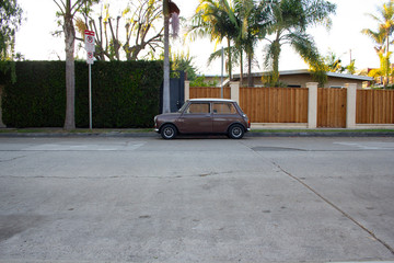 cute tiny little brown car parked in front of fences and palm trees
