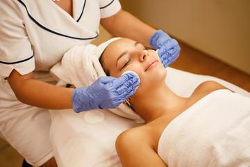 Fototapeta Young woman enjoying in beauty treatment at the spa.