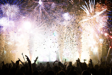 Stage lights and crowd of audience with hands raised at a music festival. Fans enjoying the party vibes. New Years Eve concept. Wall mural