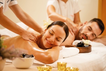 Happy couple enjoying a day at spa while having back massage.