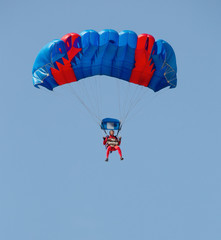 Red and blue parachute with paratrooper in sky