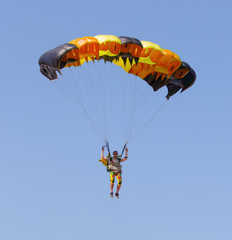 Skydiver under canopy of parachute in blue sky