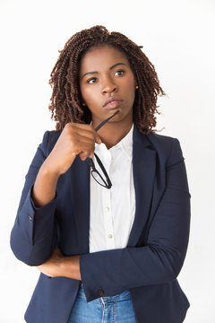Pensive female manager holding glasses. Young African American business woman standing Isolated over white background, touching face with eyewear, looking away. Professional portrait concept