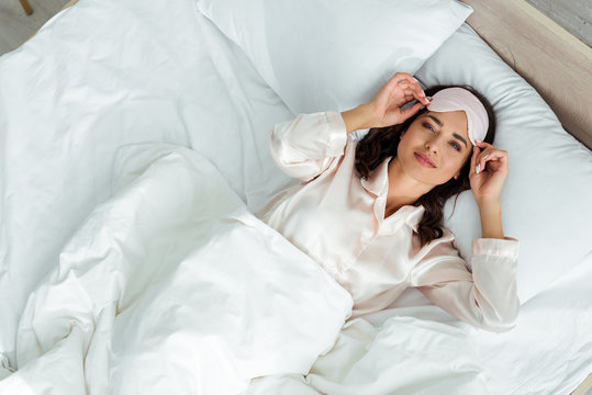 top view of attractive woman in sleeping mask lying in bed at morning