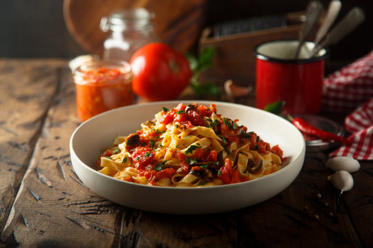 Homemade pasta with tomato sauce and olives