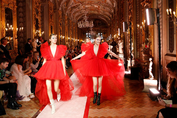 Two models on the catwalk wear a red tulle plunge-v neck asymetrical dress, paired with high-heeled shoes at a fashion show to present creations of designer Giambattista Valli and fast-fashion giant H&M in Rome