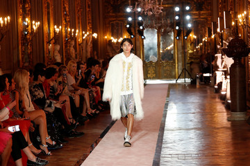 A model walks on catwalk wearing a white fake fur coat during fashion show to present creations of designer Giambattista Valli and fast-fashion giant H&M