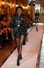 A model walks down the catwalk wearing a short black asymetrical layered dress during the fashion show to present creations of designer Giambattista Valli and fast-fashion giant H&M in Rome