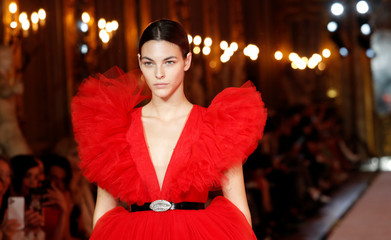 A model walks on catwalk wearing a red tulle dress during fashion show to present creations of designer Giambattista Valli and fast-fashion giant H&M in Rome