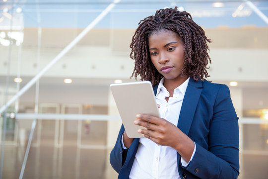 Focused professional using app on tablet outside. Young African American business woman holding digital device, looking at screen, smiling. Online app concept