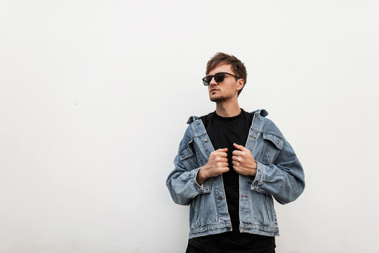 Young trendy american man hipster with a beard with a hairstyle in a stylish denim blue jacket in a black t-shirt in fashionable sunglasses posing near a vintage white wall in the city. Attractive guy