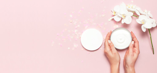 Young woman holding a opened container with cosmetic cream lotion body milk White Phalaenopsis orchid flowers festive confetti on pink background Flat lay top view minimalism style Beauty concept