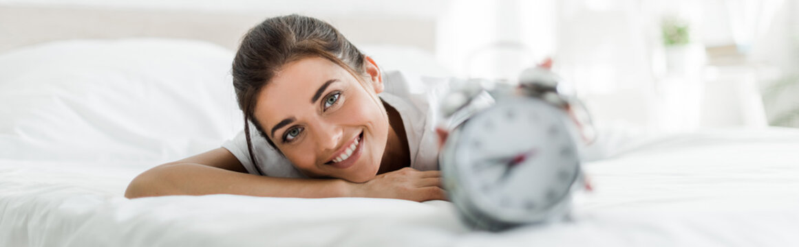selective focus of happy girl lying with alarm clock on bed in the morning
