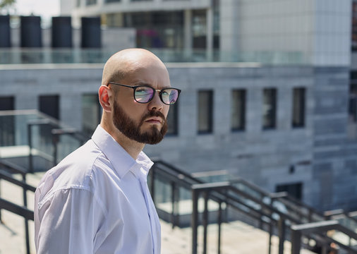 A bald young guy in glasses and with a dark beard on the street on the steps looking sideway against the background of a building in city. Worker, employee, employment. Business.