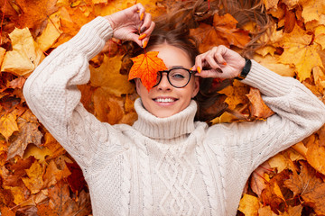Funny young hipster woman with a positive smile with an orange maple leaf in glasses in a trendy knitted sweater lies on autumn foliage in the park. Joyful girl holds in a hand golden leaf near face.