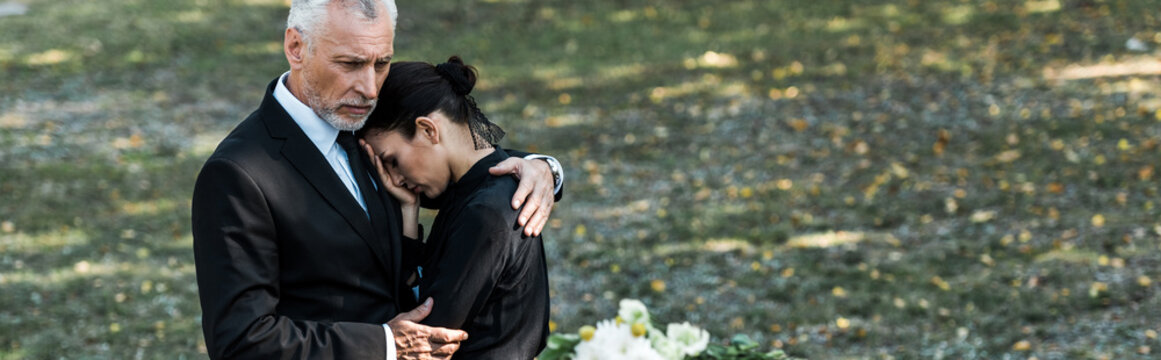 panoramic shot of bearded man hugging attractive woman on funeral
