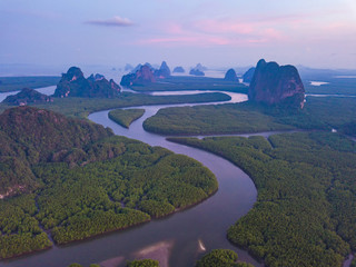 Aerial top view of Samet Nangshe, mountain valley hills, and tropical green forest trees at sunset with Andaman sea in Phang Nga Bay in summer, Thailand in travel trip. Natural landscape background.