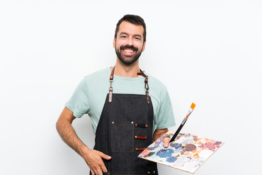 Young artist man holding a palette over isolated background laughing