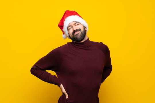 Man with christmas hat over isolated yellow background suffering from backache for having made an effort