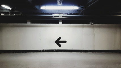 Illuminated Underground Parking Lot with Black Directional Arrow on Concrete Wall Fototapete
